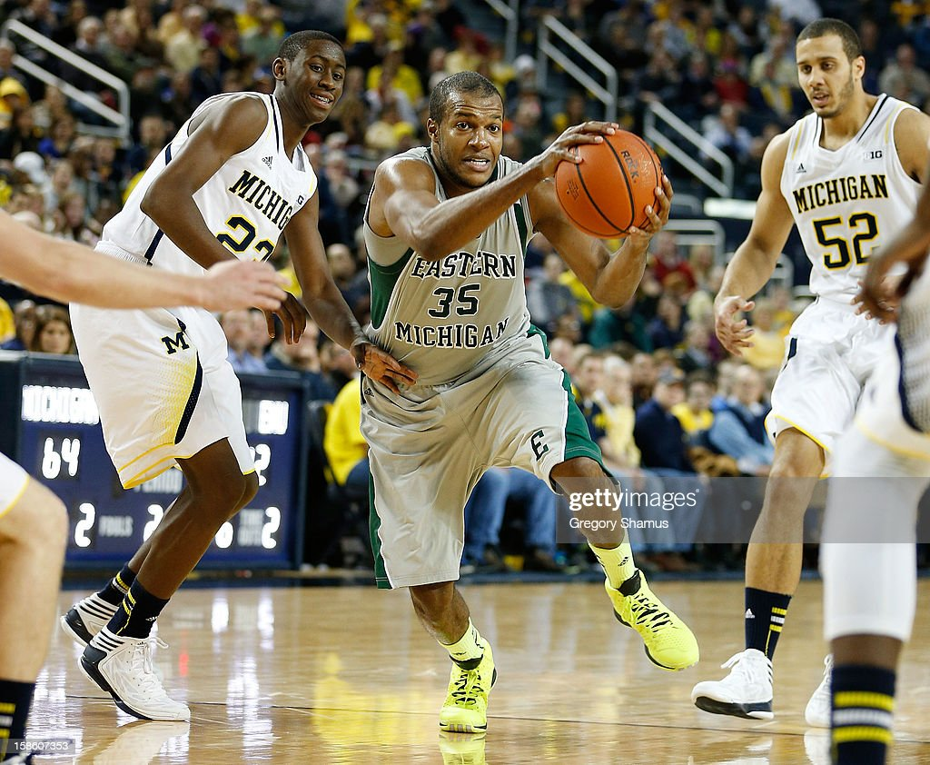 Daylen Harrison #35 of the Eastern Michigan Eagles drives between the defense of Caris LeVert #23 and Jordan Morgan #52 of the Michigan Wolverines at Crisler Center on December 20, 2012 in Ann Arbor, Michigan.
