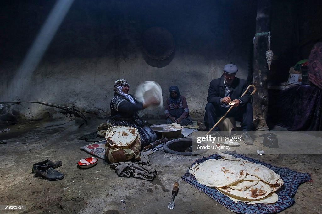 Daylight enters through holes in the ceiling in a village kitchen as women make bread in traditional tandoor which is a cylindrical clay or metal...