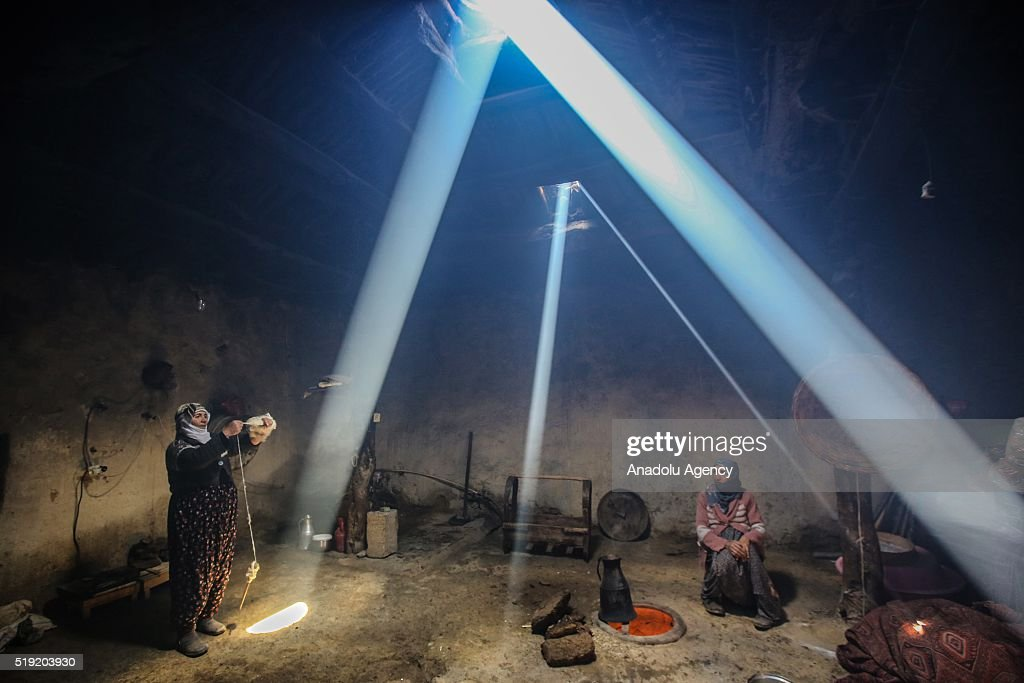 Daylight enters through holes in the ceiling in a village kitchen as women cook in traditional tandoor which is a cylindrical clay or metal oven used...