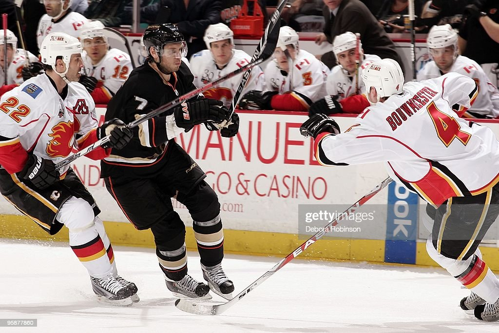Daymond Langkow and Jay Bouwmeester of the Calgary Flames defend against Steve Eminger of the Anaheim Ducks during the game on January 17 2010 at...