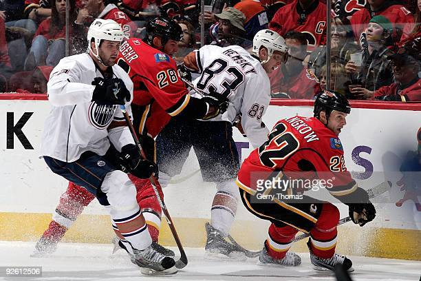 Daymond Langkow and Robyn Regehr of the Calgary Flames skate against Dustin Penner and Ales Hemsky of the Edmonton Oilers on October 24 2009 at...