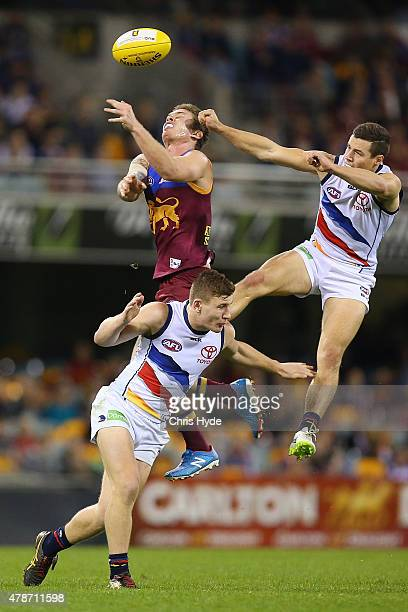 Dayne Beams of the Lions and Rory Laird and Luke Brown of the Crows compete for a mark during the round 13 AFL match between the Brisbane Lions and...