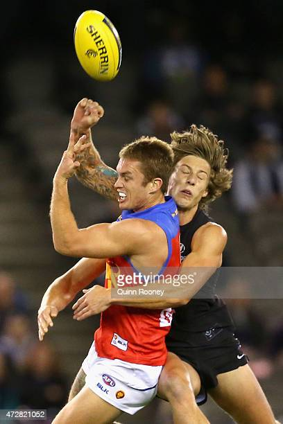 Dayne Beams of the Lions handballs whilst being tackled Mark Whiley of the Blues during the round six AFL match between the Carlton Blues and the...
