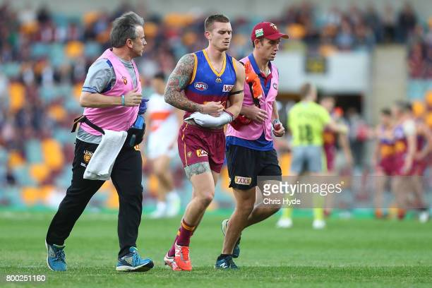 Dayne Beams of the Lions leaves the field injured during the round 14 AFL match between the Brisbane Lions and the Greater Western Sydney Giants at...