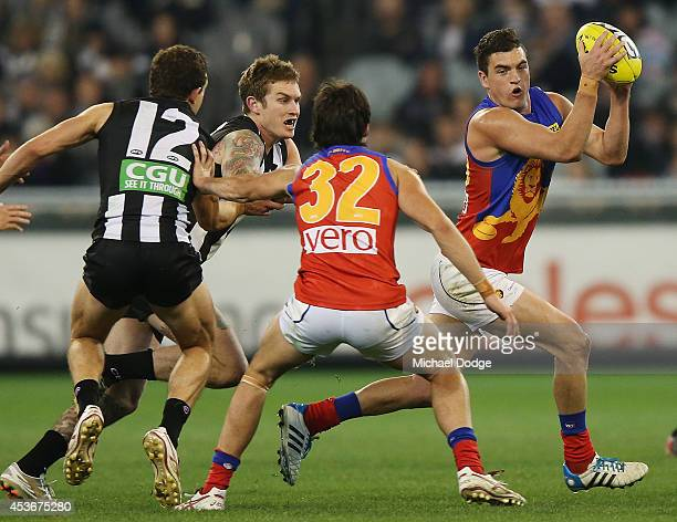 Dayne Beams of the Magpies chases Tom Rockliff of the Lions during the round 21 AFL match between the Collingwood Magpies and the Brisbane Lions at...