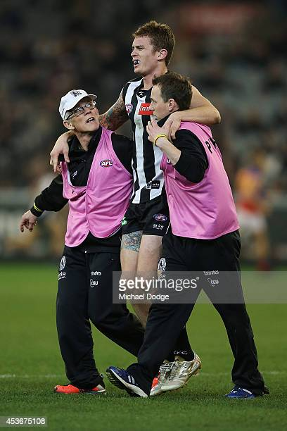 Dayne Beams of the Magpies is helped off after a leg injury during the round 21 AFL match between the Collingwood Magpies and the Brisbane Lions at...
