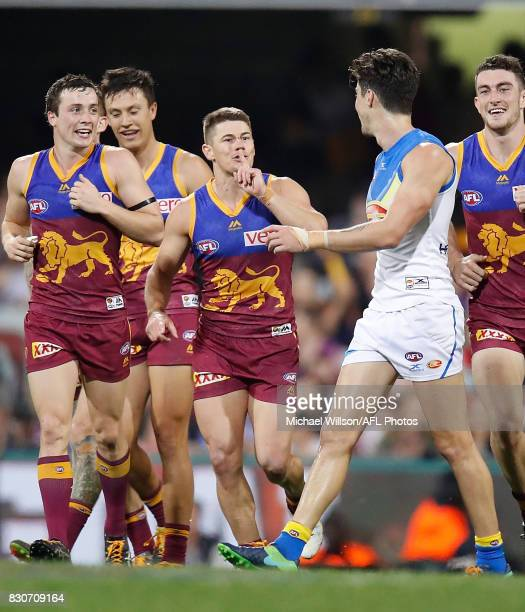 Dayne Zorko of the Lions gestures to Alex Sexton of the Suns after kicking a goal during the 2017 AFL round 21 match between the Brisbane Lions and...