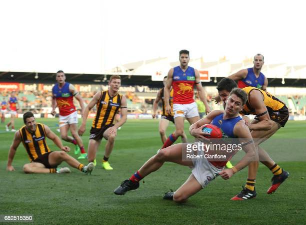 Dayne Zorko of the Lions is challenged by Ryan Burton of the Hawks during the round eight AFL match between the Hawthorn Hawks and the Brisbane Lions...