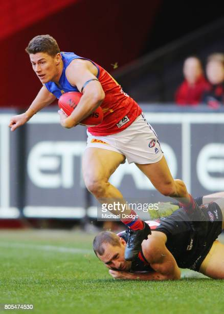 Dayne Zorko of the Lions runs with the ball from James Kelly of the Bombers during the round 15 AFL match between the Essendon Bombers and the...