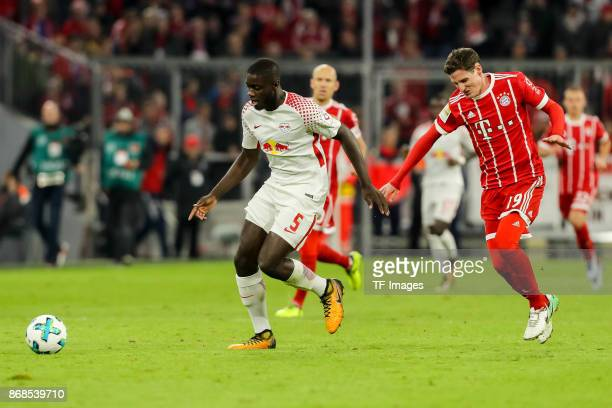 Dayot Upamecano of Leipzig and Sebastian Rudy of Muenchen battle for the ball during the Bundesliga match between FC Bayern Muenchen and RB Leipzig...