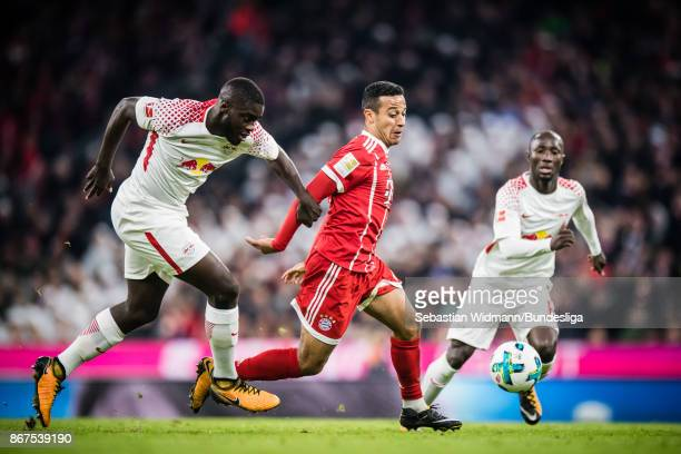 Dayot Upamecano of Leipzig and Thiago Alcantara of FC Bayern Muenchen compete for the ball during the Bundesliga match between FC Bayern Muenchen and...