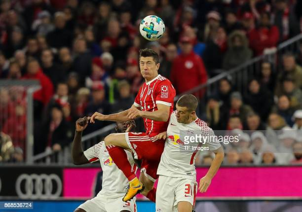 Dayot Upamecano of Leipzig Diego Demme of Leipzig and Robert Lewandowski of Muenchen battle for the ball during the Bundesliga match between FC...