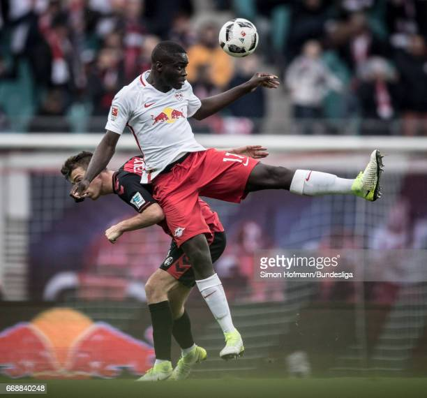Dayot Upamecano of Leipzig jumps for a header with Janik Haberer of Freiburg during the Bundesliga match between RB Leipzig and SC Freiburg at Red...