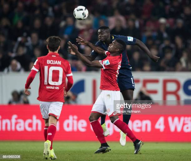 Dayot Upamecano of Leipzig jumps for a header with Jhon Cordoba of Mainz during the Bundesliga match between 1 FSV Mainz 05 and RB Leipzig at Opel...