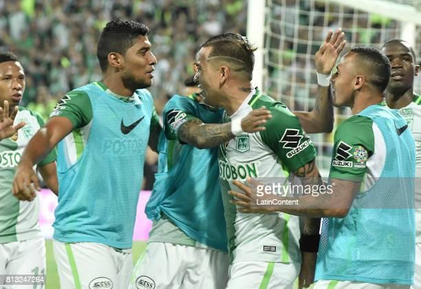 Dayro Moreno of Atletico Nacional celebrates with teammates Luis Carlos Ruiz and Aldo Leao Ramirez after scoring the fourth goal of his team during...