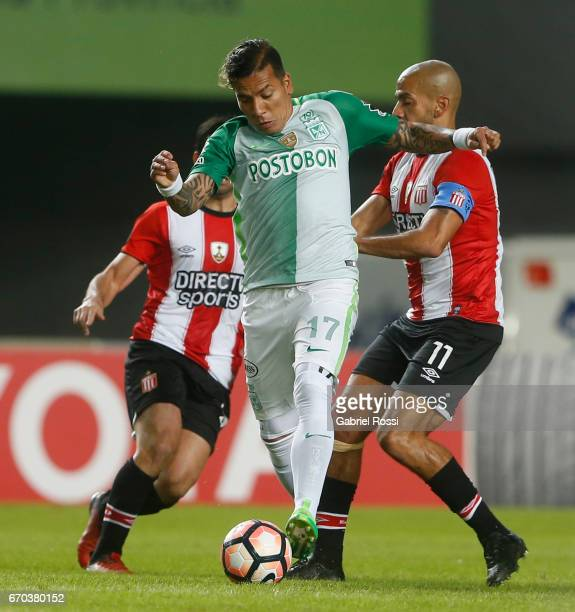 Dayro Moreno of Atletico Nacional defends the ball from Juan Sebastian Veron of Estudiantes during a group stage match between Estudiantes and...