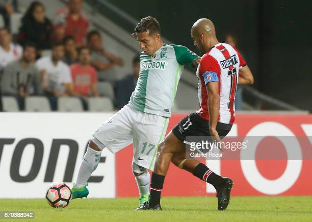 Dayro Moreno of Atletico Nacional fights defends the ball from Juan Sebastian Veron of Estudiantes during a group stage match between Estudiantes and...