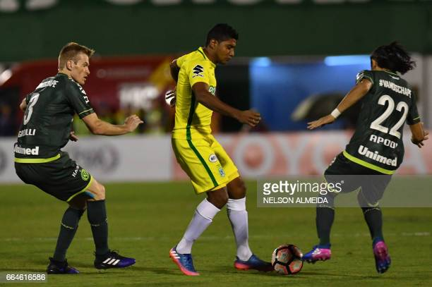 Dayro Moreno of Colombia's Atletico Nacional vies for the ball with Douglas Grolli and Apodi of Brazil's Chapecoense during their Recopa Sudamericana...