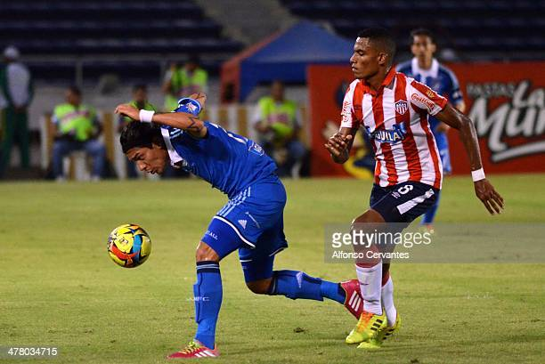 Dayro Moreno of Millonarios struggles for the ball with William Tesillo of Junior during a match between Junior and Millonarios as part of round 10...