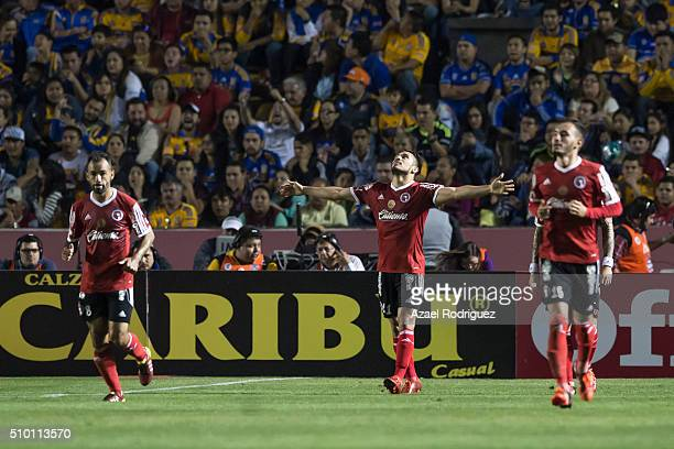 Dayro Moreno of Tijuana celebrates with teammates after scoring his team's first goal during the 6th round match between Tigres UANL and Tijuana as...
