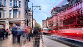 Daytime long exposure on Oxford Street near Oxford Circus on a busy weekend afternoon as shoppers walk past and several buses drive by.