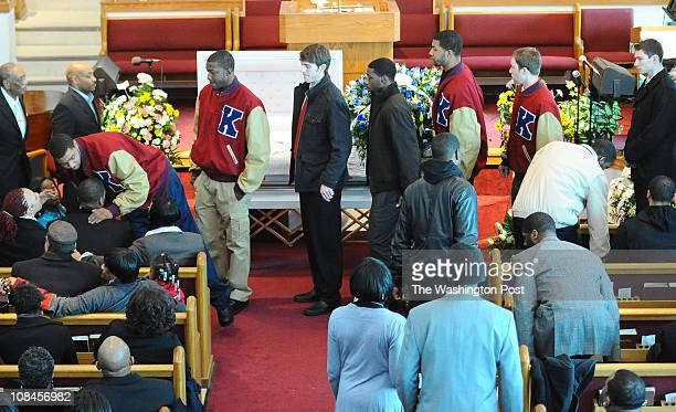 Members of the University of Kansas basketball team line up to console their teammate forward Thomas Robinson at the funeral for his mother Lisa...