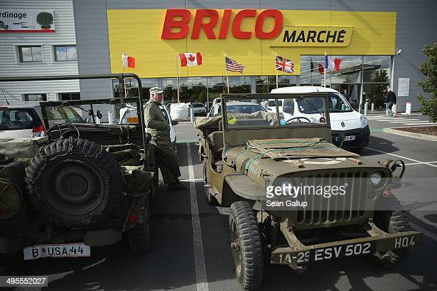 Day historical reenactment enthusiast from the United Kingdom dressed as a US soldier waits by World War IIera jeeps as his buddies shop in a...