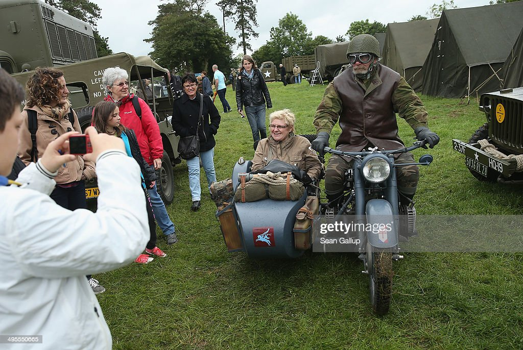 D-Day re-enactment enthusiasts dressed as Allied soldiers ride a World War II-era motorcycle and sidecar through a re-enactment camp on June 4, 2014 in Sainte Mere Eglise, France. Friday the 6th of June is the 70th anniversary of the D-Day landings that saw 156,000 troops from the Allied countries, including the United Kingdom and the United States, join forces to launch an audacious attack on the beaches of Normandy, these assaults are credited with the eventual defeat of Nazi Germany. A series of events commemorating the 70th anniversary are planned for the week with many heads of state travelling to the famous beaches to pay their respects to those who lost their lives.
