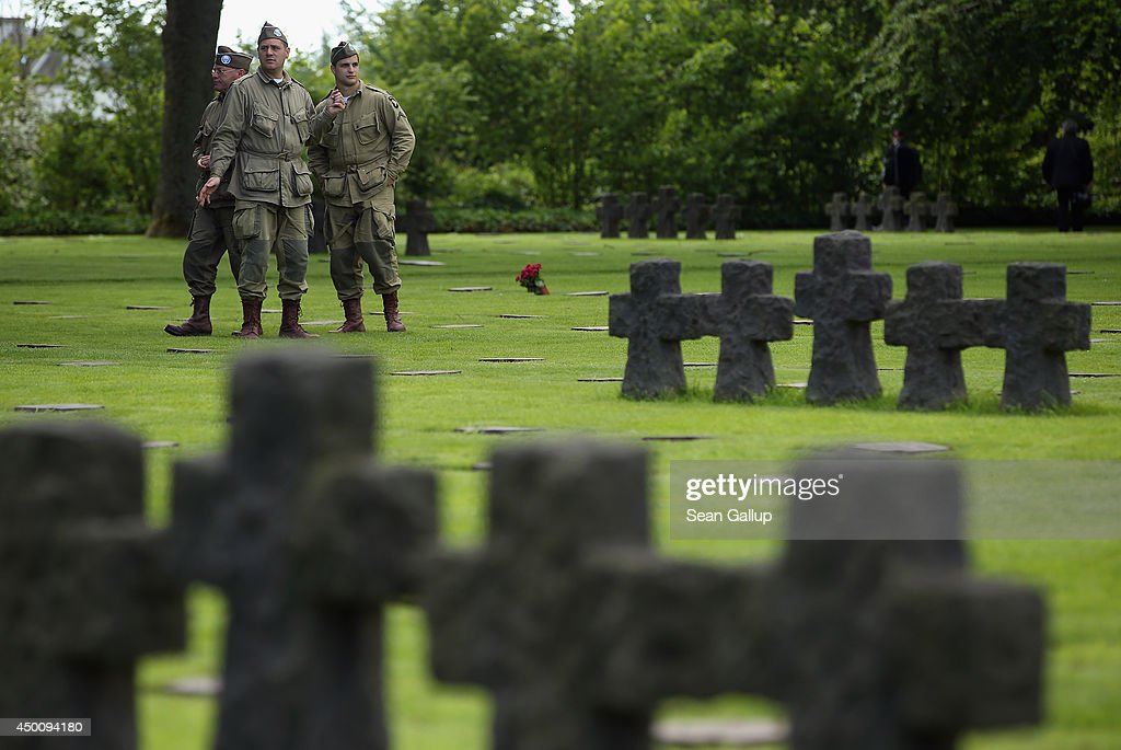 D-Day re-enactment enthusiasts dressed as World War II American soldiers walk among gravestones at the German Cemetery where approximately 21,000 German World War II soldiers are buried on June 5, 2014 at La Cambe, France. Friday the 6th of June is the 70th anniversary of the D-Day landings that saw 156,000 troops from the Allied countries, including the United Kingdom and the United States, join forces to launch an audacious attack on the beaches of Normandy, these assaults are credited with the eventual defeat of Nazi Germany. A series of events commemorating the 70th anniversary are planned for the week with many heads of state travelling to the famous beaches to pay their respects to those who lost their lives.