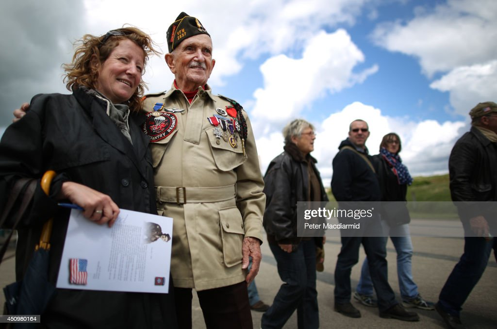 Day veteran Jack Schlegel (1923-2014) stands with admirers at Utah beach on June 4, 2014 near Saint Marie du Mont, France. Friday 6th June is the 70th anniversary of the D-Day landings which saw 156,000 troops from the allied countries including the United Kingdom and the United States join forces to launch an audacious attack on the beaches of Normandy, these assaults are credited with the eventual defeat of Nazi Germany.