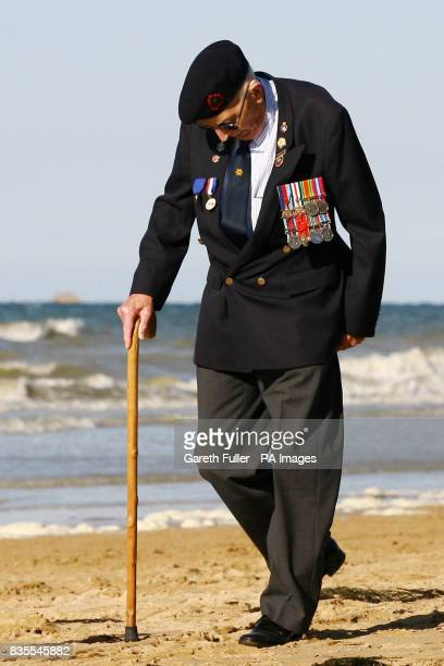 DDay veteran Percy Lewis of the 1st Buckinghamshire Battalion during World War Two walks along the beach in Arromanches France ahead of the 65th...