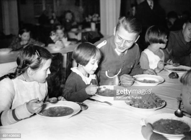 De très jeunes enfants déjeunent accompagnés par un représentant des Jeunesses Hitlériennes le 6 novembre 1935 à Berlin Allemagne