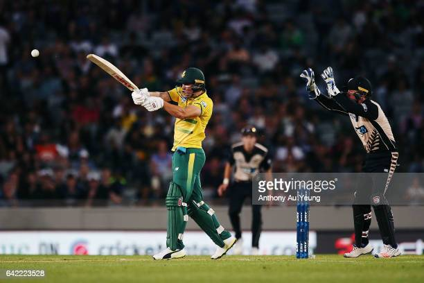 AB de Villiers of South Africa bats as Luke Ronchi of New Zealand looks on during the first International Twenty20 match between New Zealand and...
