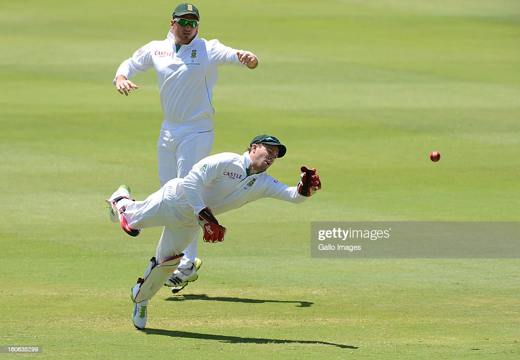 AB de Villiers of South Africa dives with <a gi-track='captionPersonalityLinkClicked' href=/galleries/search?phrase=Graeme+Smith+-+Cricket+Player&family=editorial&specificpeople=193816 ng-click='$event.stopPropagation()'>Graeme Smith</a> looking on during day 4 of the 1st Test match between South Africa and Pakistan at Bidvest Wanderers Stadium on February 4, 2013 in Johannesburg, South Africa.