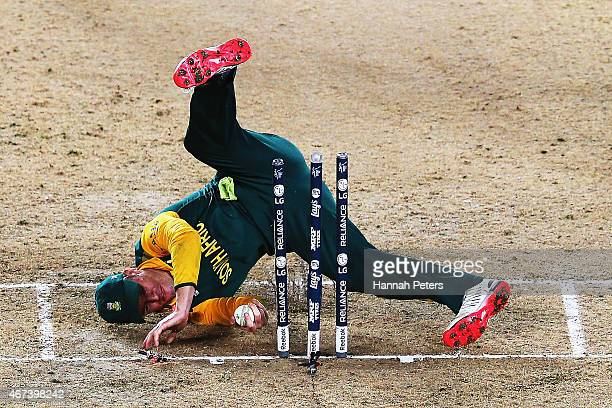 AB de Villiers of South Africa falls over the stumps during the 2015 Cricket World Cup Semi Final match between New Zealand and South Africa at Eden...