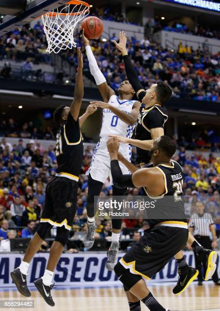 De'Aaron Fox of the Kentucky Wildcats shoots against Landry Shamet Shaquille Morris and Darral Willis Jr #21 of the Wichita State Shockers in the...