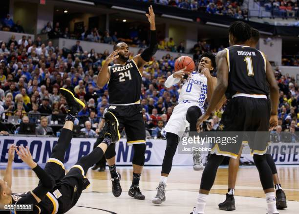 De'Aaron Fox of the Kentucky Wildcats tries to hold onto the ball against Shaquille Morris and Zach Brown of the Wichita State Shockers in the first...