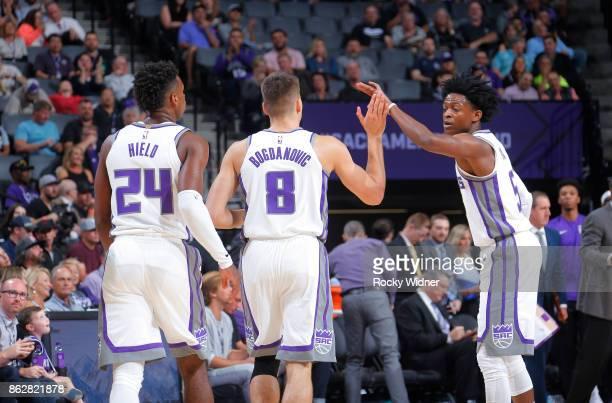 De'Aaron Fox of the Sacramento Kings high fives teammates Bogdan Bogdanovic and Buddy Hield during the game against the San Antonio Spurs on October...