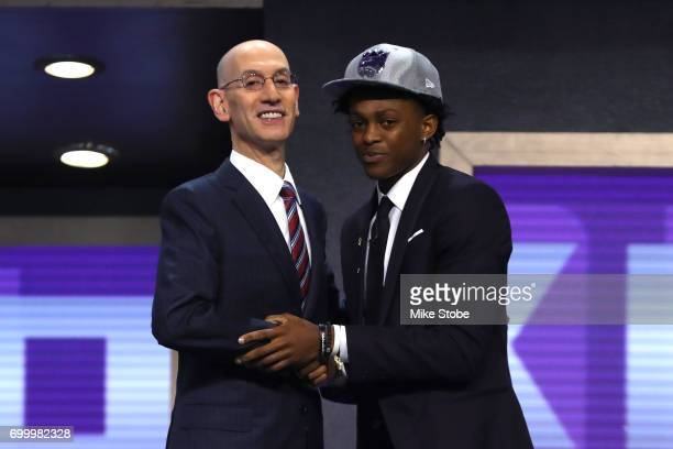 De'Aaron Fox walks on stage with NBA commissioner Adam Silver after being drafted fifth overall by the Sacramento Kings during the first round of the...