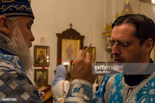 A deacon at the Synodal Cathedral is anointed with oil by Bishop Gabriel of Montreal On the eve of the Feast of the Dormition of the Virgin the...