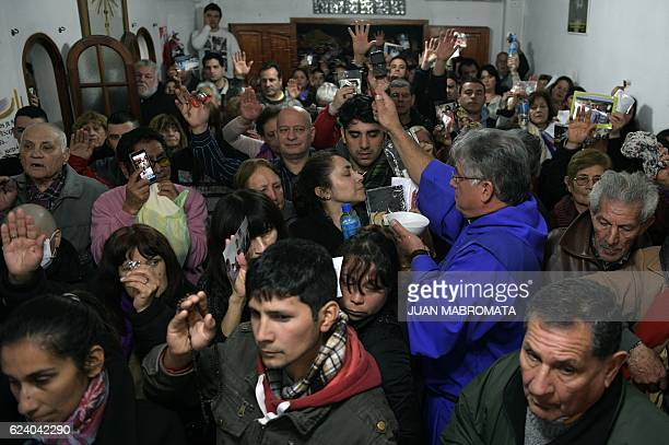 Deacon Jorge Ott blesses parishioners holding pictures of relatives during a ritual at the 'El Buen Pastor' parish in Santos Lugares outskirts of...