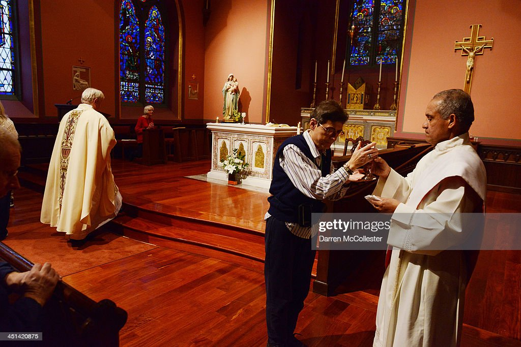 Deacon Luciano Herrera (R) gives communion to a parishioner during a mass to commemorate the 50th anniversary of the assassination of John F. Kennedy at the Blessed Sacrament Chapel in the Cathedral of the Holy Cross November 22, 2013 in Boston, Massachusetts. Kennedy, born in Brookline Massachusetts, was killed 50 years ago on this day by Lee Harvey Oswald in Dallas Texas in 1963.