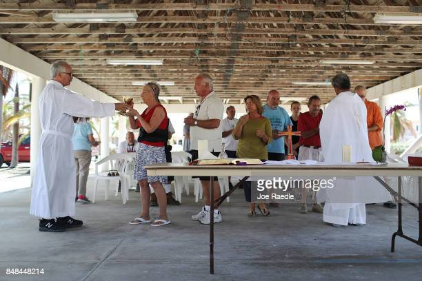 Deacon Richard Turcotte and Rev Jets Medina hold communion as they lead a mass for their congregation of St Peter Catholic Church under a pavillion...