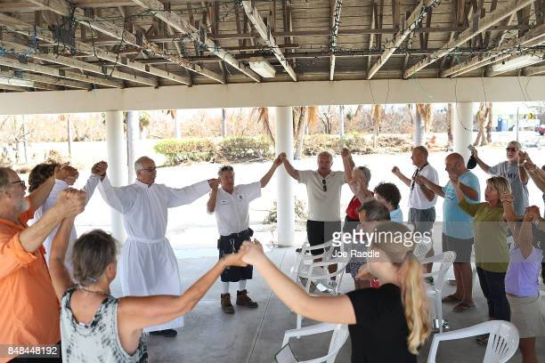 Deacon Richard Turcotte leads a mass for his congregation of St Peter Catholic Church under a pavilion after their church was damaged by hurricane...