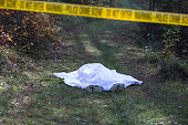 Dead corpse on a road in woods covered with white blanket and enclosed with the yellow tape