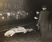 A dead body lies on a cobblestone street covered by paper newspaper and a shoe police officer and perhaps a priest stand near by and a crowd watches...