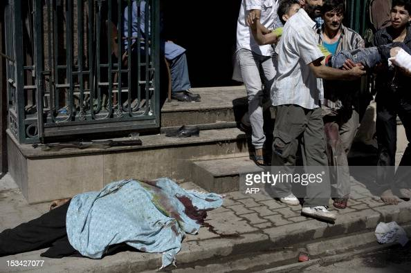 A dead body lies on the ground as Syrians carry a relative who was wounded from shelling on a refugee center by government forces outside the Dar...