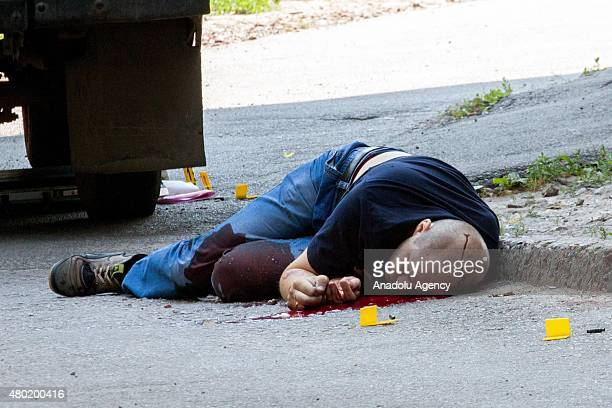 A dead body of a victim lies on the ground after an armed attack on a postoffice money courier vehicle in Kharkiv Ukraine on July 10 2015 Attackers...