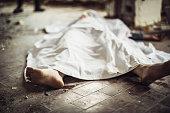 Dead body covered with sheet on murder crime scene