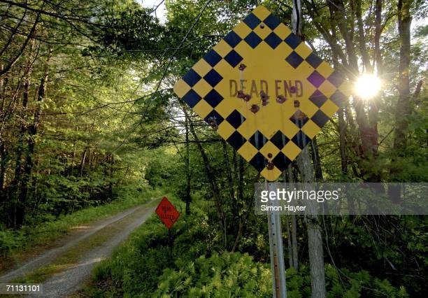 A 'Dead End' and a 'Road Closed' sign lie at the entrance way to an alleged terrorist training camp June 5 2006 in Washago located north of Toronto...